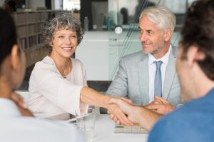 Close up of a cheerful senior business woman shaking hands with businessman. Business people shaking hands in meeting. Handshake between mature leadership and young business man.
